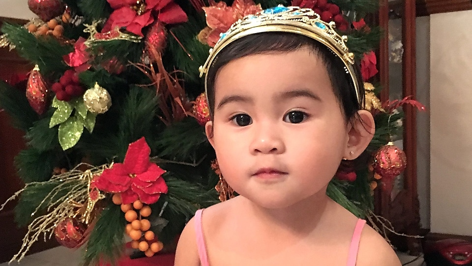 Close up of Jason's two-year-old girl, Isabelle, in front of a Christmas tree