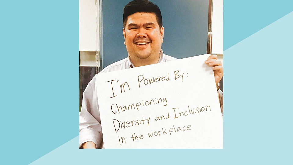 Ruel holds a large card saying 'I'm Powered By: Championing Diversity and Inclusion in the workplace'