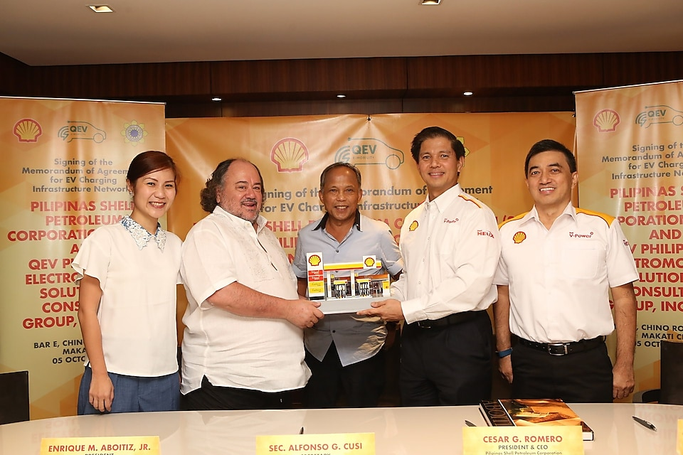 Endika Aboitiz (2nd from left), President of QEV Philippines Electromobility Solutions and Consulting Group, Inc., accepts a miniature replica of a Shell retail station from Cesar Romero, President and CEO of PSPC
