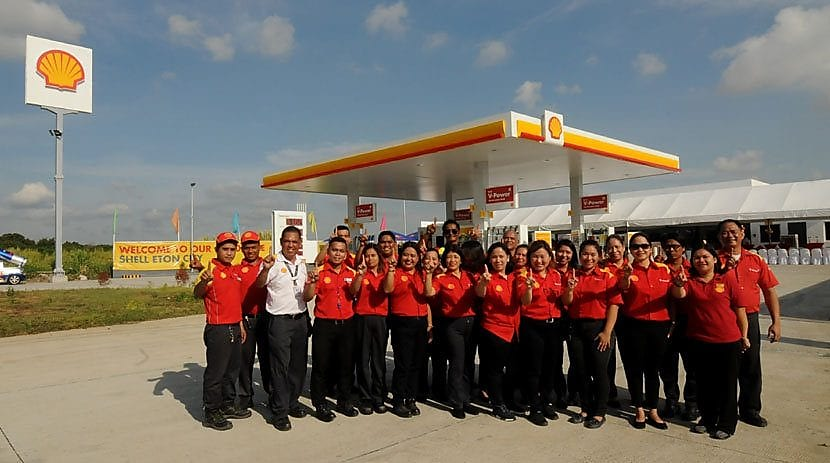 people standing near shell station for photo