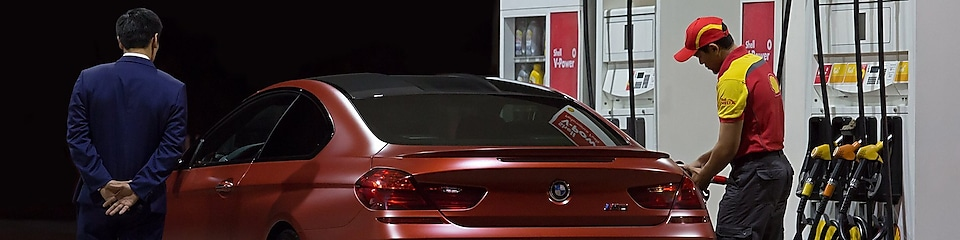 service attendant fuelling red bmw