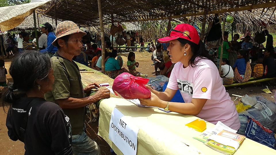A volunteer distributing long-lasting insecticide-treated nets to locals