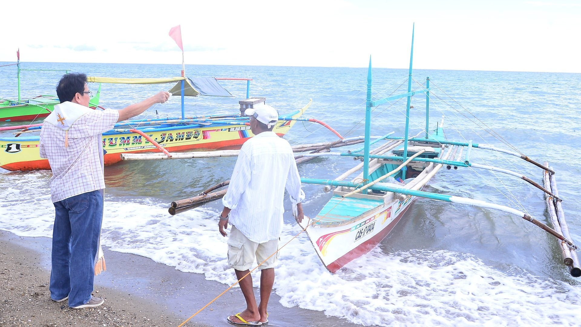 A priest blessing the boats of the fishermen beneficiaries alt-text: A priest blessing boats of beneficiaires
